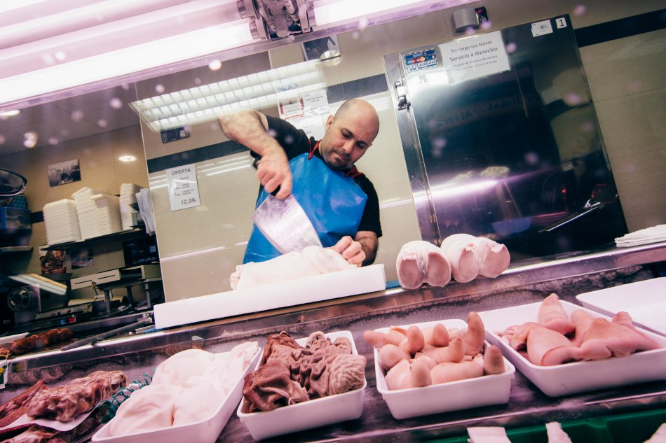 """Luis Alvarez Jimenez, 44, has been working in Mercado de Antón Martín in Madrid for 12 years. He sells bull meat, pork, and lamb. """"I love my job,"""" he stated. """"I love attending the public."""""""