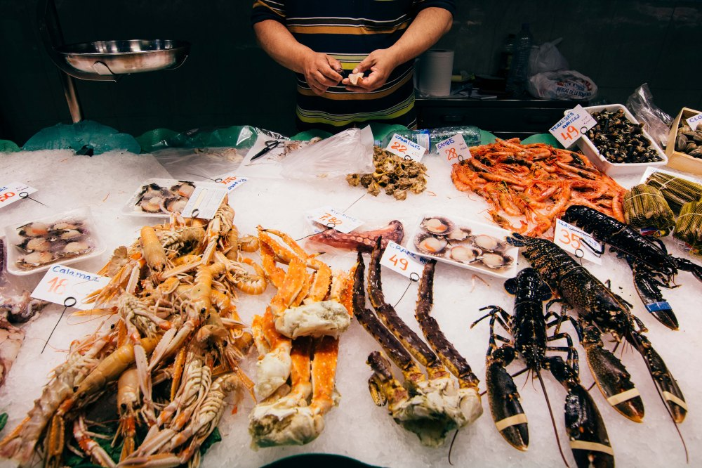 A man prepares squid in La Boqeria. His stall has shrimps, crabs, lobsters and clams.