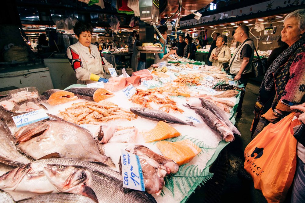 Shoppers croud around the seafood stalls in La Boqueria that have lloborro, a European seabass, salmon, razor clams and shrimp.