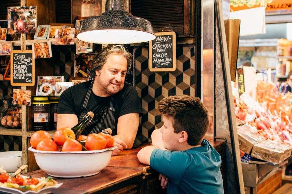 """Pablo Burcaizea, the owner of a crêperie stand in La Boqerilla, talks to Javi, 12, the nephew of one of the vendors who sells ham, one of the oldest stores in the market. """"We have been friends for his whole life, since he's younger."""" He's been in the market since he was a baby in a carriage. """"If the market needed a mascot, they don't need to hire it – we already have him. He will be the logo of the market,"""" said Burcaizea. """"I love the international influence, how cosmopolitan this market is."""""""