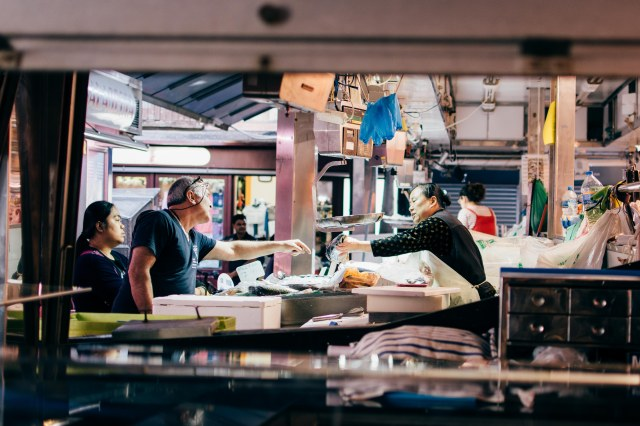 A woman hands Hake, a deep sea fish over to a customer in La Boqueria. Spain is the highest consumer of Hake in Europe.