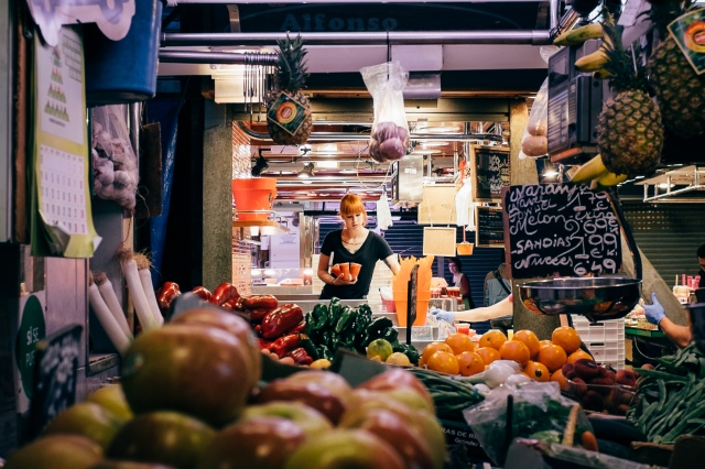 A woman arranges fruit juice as La Boqueria opens at 8 in the morning.